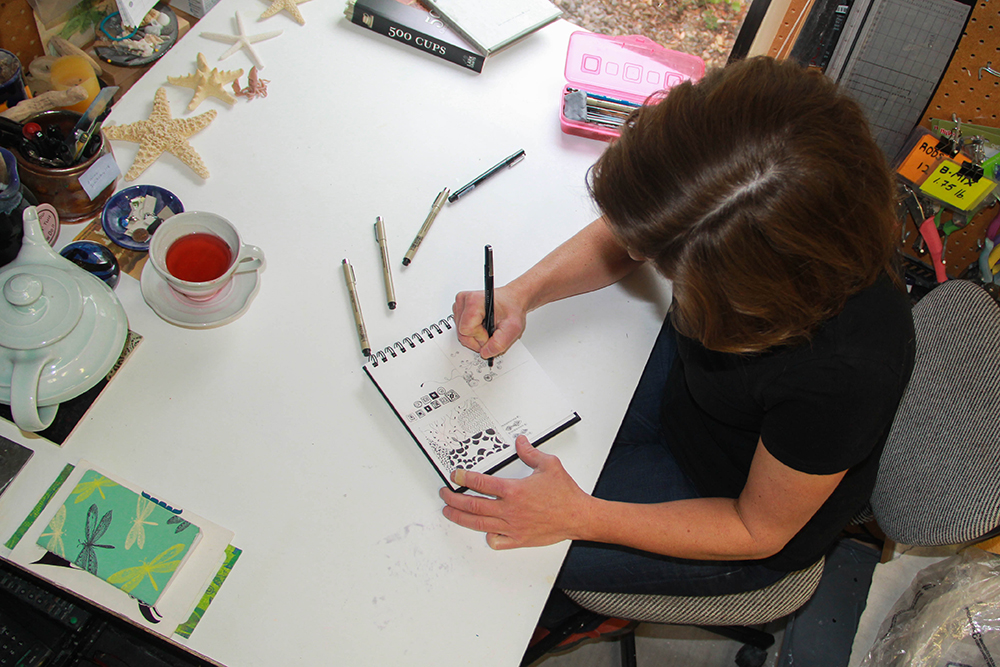 Jennifer C Vigil in her studio drawing
