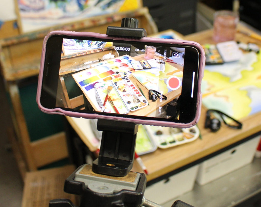 Smartphone adapter for tripods with an iPhone X video taping an art class